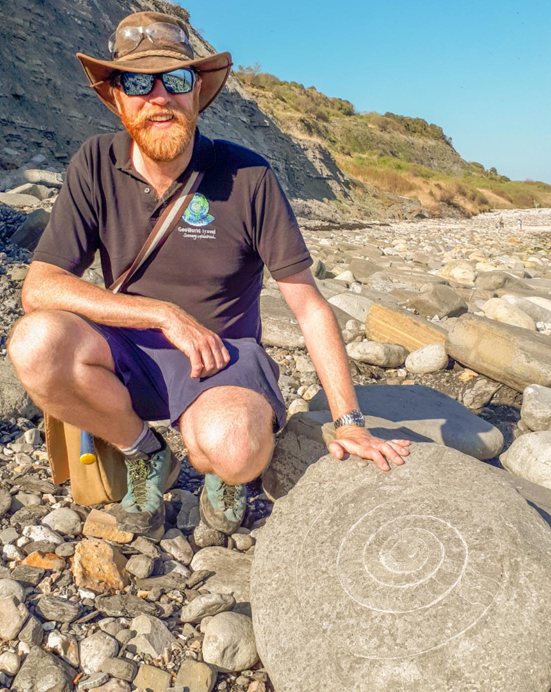 A photograph of James Cresswell, Director of GeoWorld Travel kneeling next to an ammonite in Lyme Regis on the Jurassic Coast