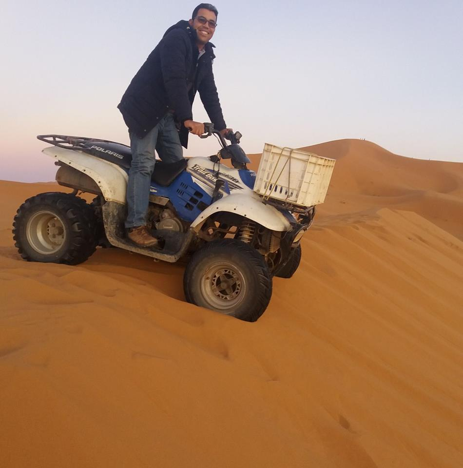 A photograph of Youssef Nomada riding a quad bike down a sand dune in Morocco