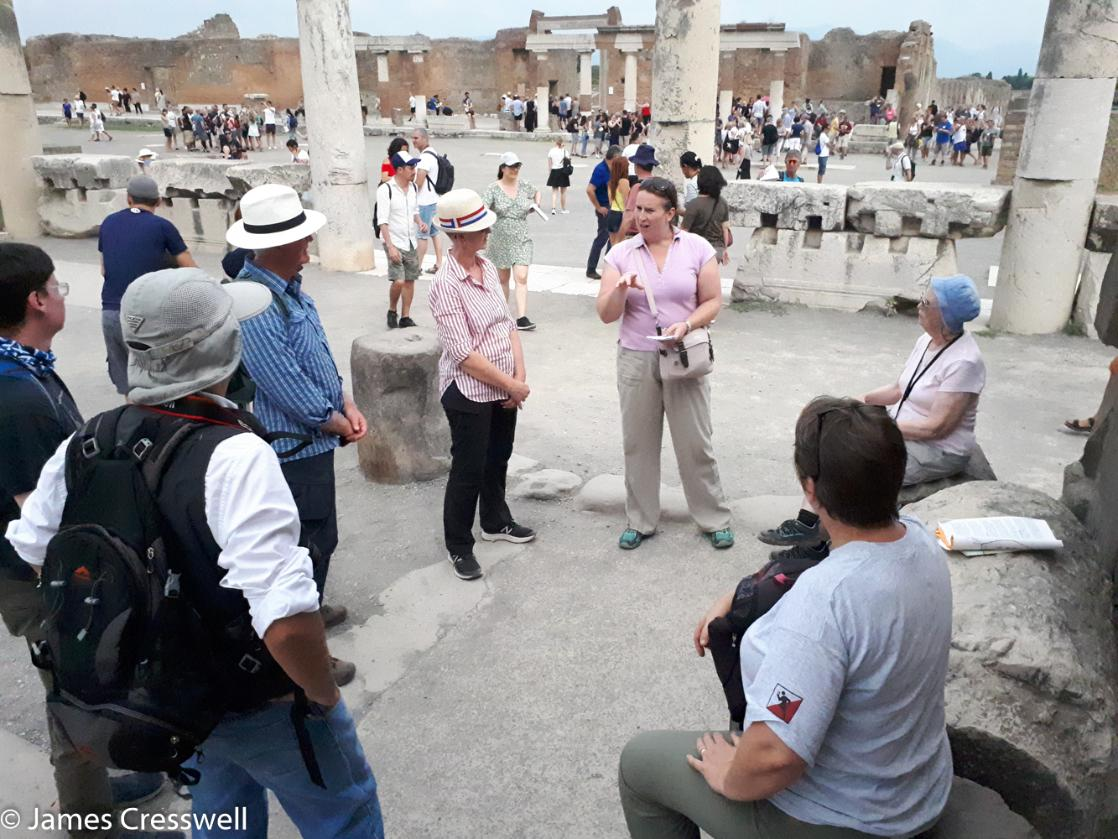A photograph of archaeologist Abby Cresswell explaing the archaeology of Pompeii on GeoWorld Travel's geology of Italy tour