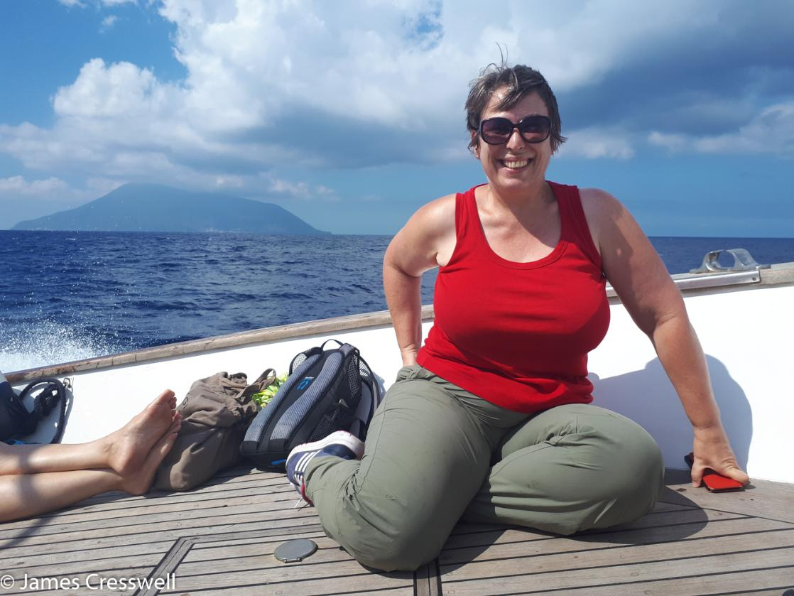 A photograph of a woman sitting on a boat with Stromboli volcano in the background taken on GeoWorld Travel's Italy volcanoes tour