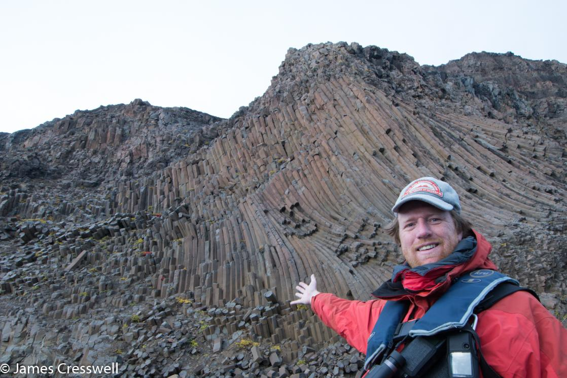 A photograph of James Cresswell pointing to columnar joints in East Greenland