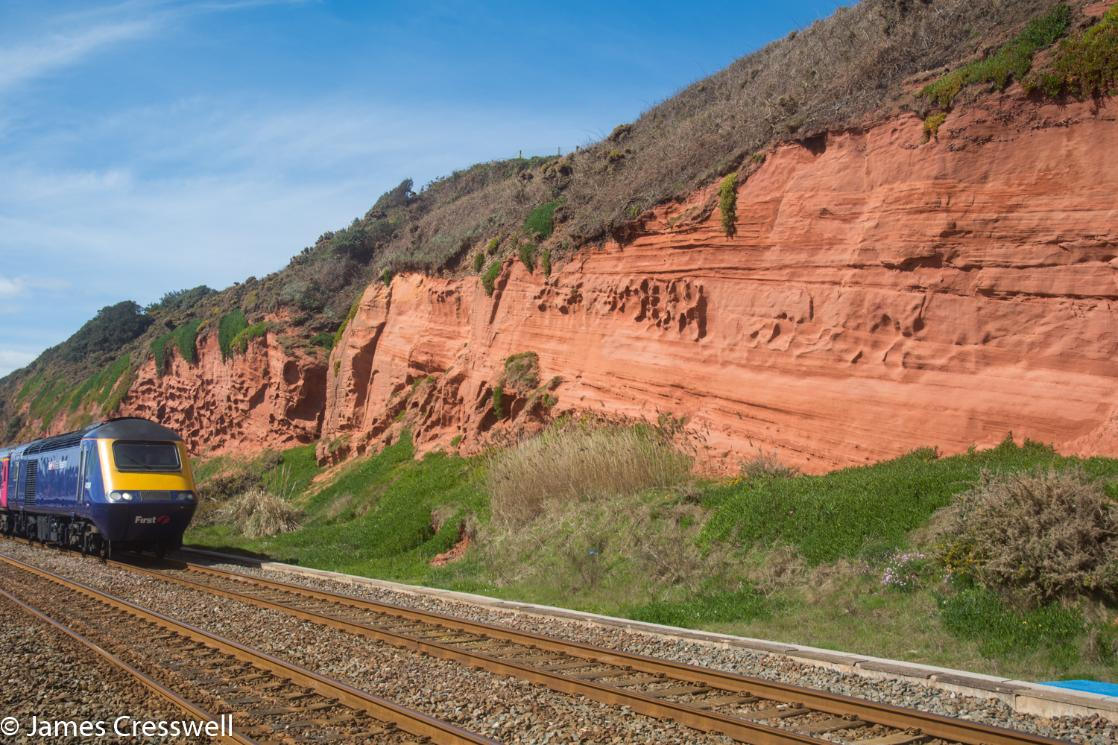 A photograph of Permain aged fossil sand dunes with a train passing in front, taken at Dawlish on the GeoWorld Travel England and Wales geology trip, tour and holiday