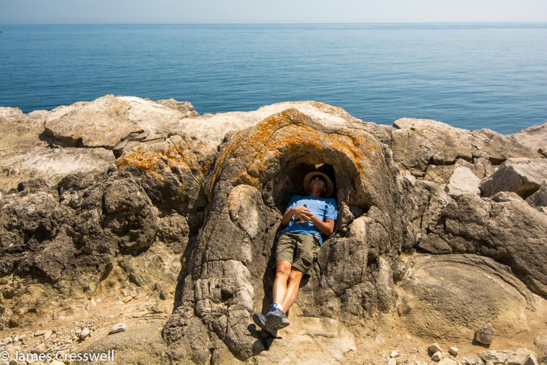 A photograph of a man lying inside a fossilised tree at Lulworth Cove, taken on the GeoWorld Travel England and Wales geology trip, tour and holiday