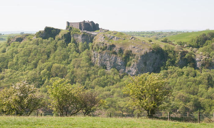 A photograph of Carreg Cennen Castle perched on top of a cliff. taken on a GeoWorld Travel Fforest Fawr Geopark geology day tour