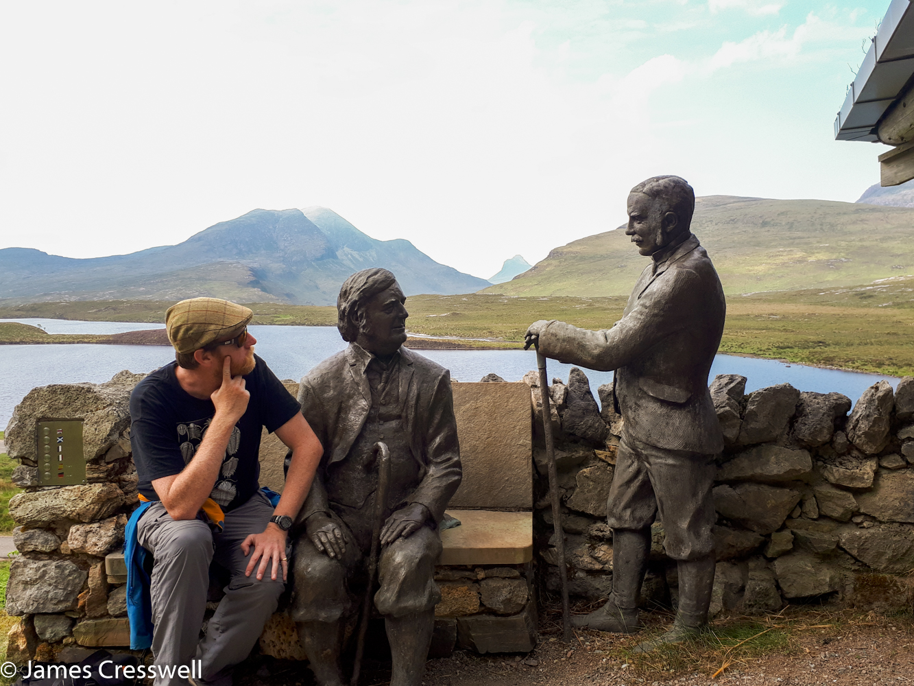 A photograph of James Cresswell with a statue of Ben Peach and John Horne at Knockan Crag, on a GeoWorld Travel History of Geology tour