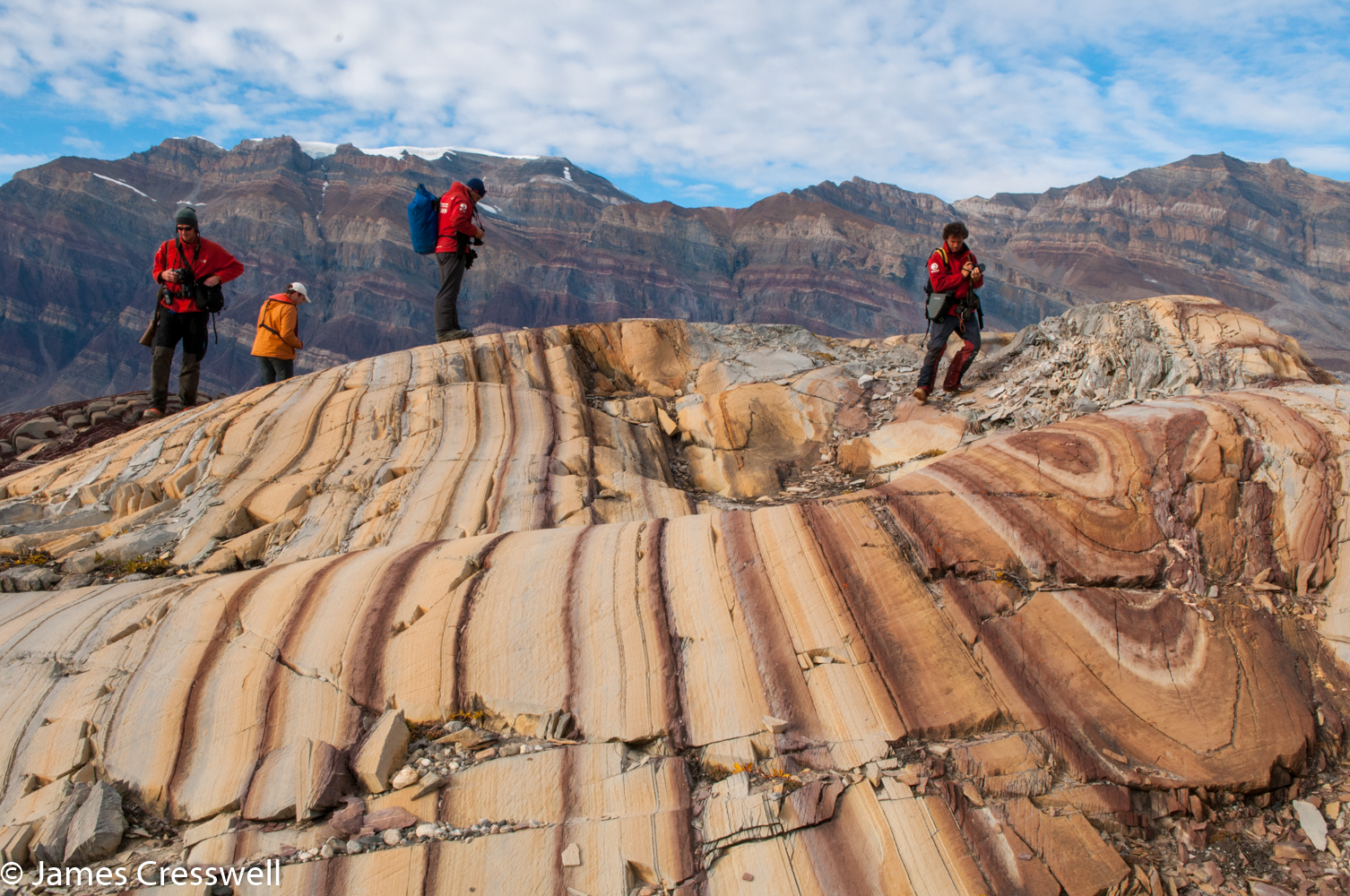 A photograph of people standing on stripy rocks, taken in east Greenland on a PolarWorld Travel placed cruise
