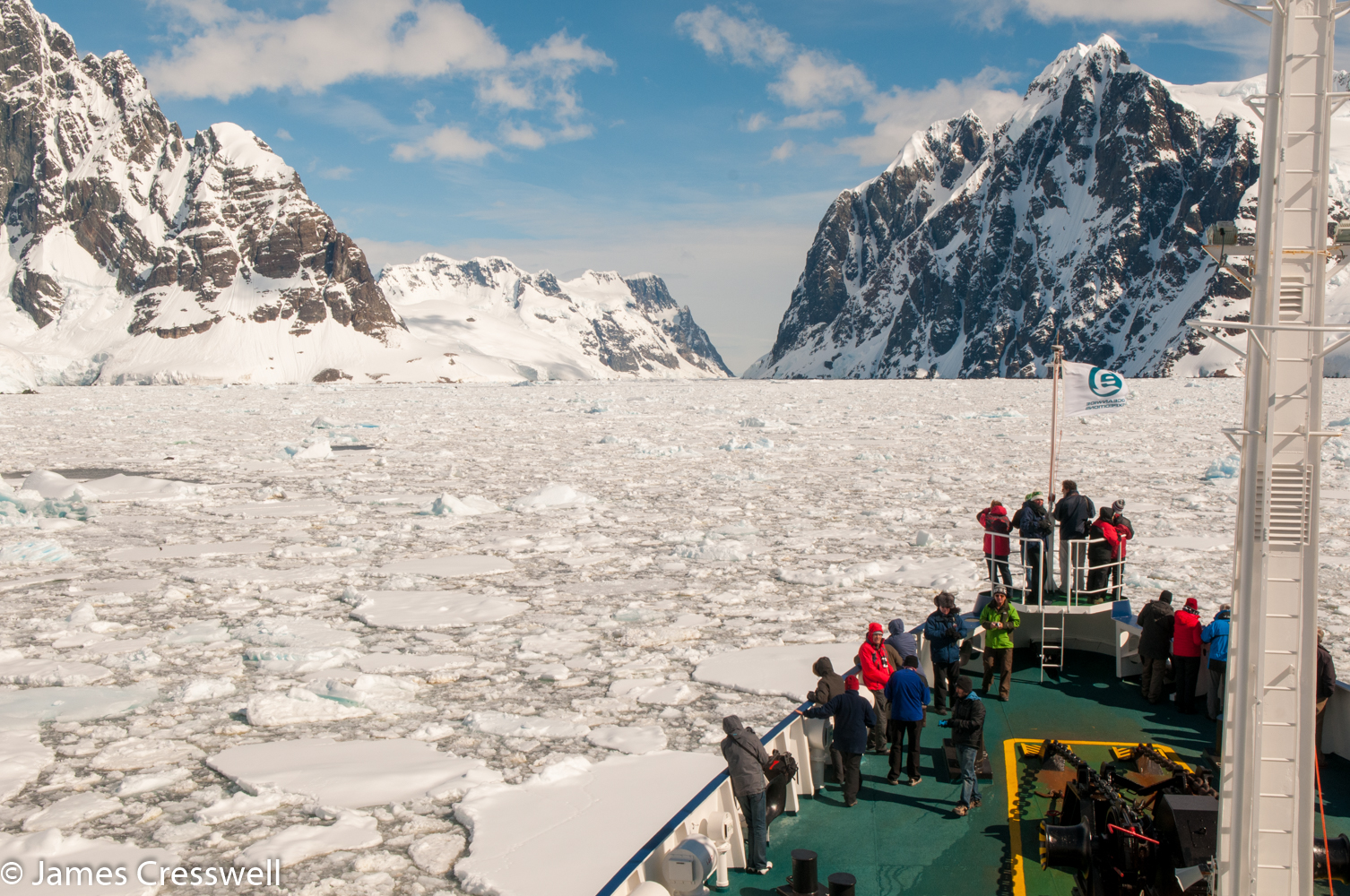 A photograph of a ship pushing through ice in Antarctica on a PolarWorld Travel placed cruise