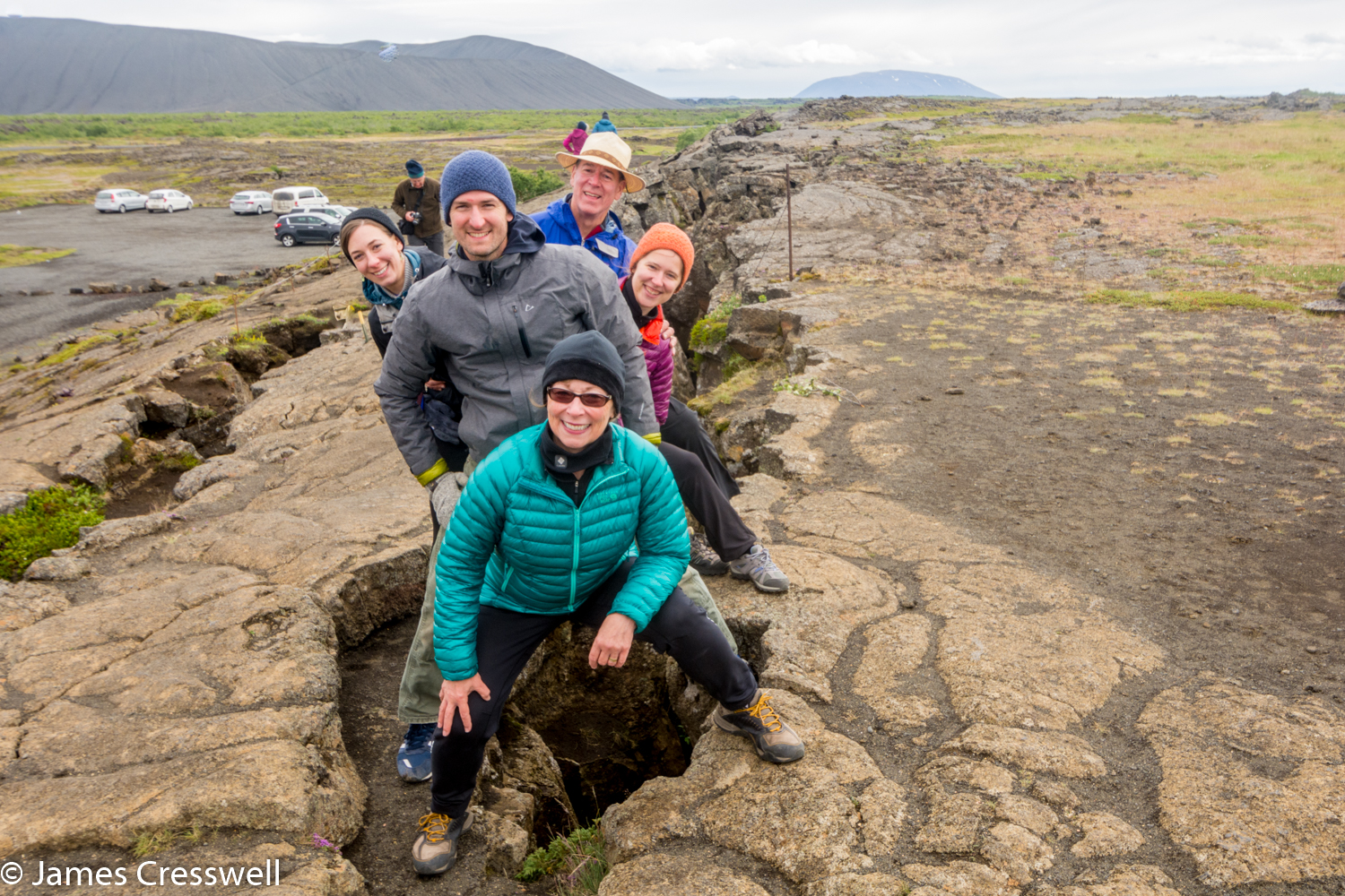 A photograph of people straddling a plate boundary, taken on a GeoWorld Travel Iceland volcano and geology trip, tour and holiday