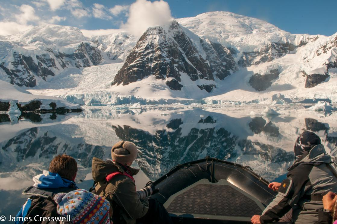 A photograph with people in the foreground admiring mountains in Antarctica, taken on a PolarWorld Travel placed expedition cruise