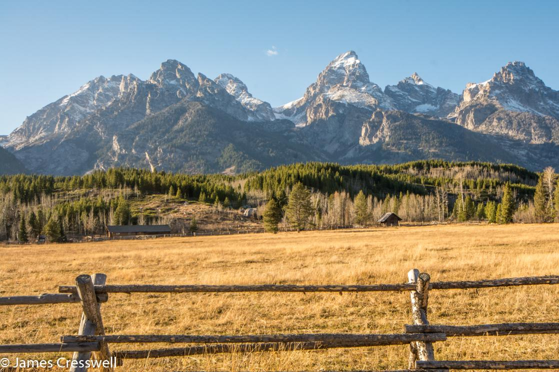 A photograph with a fence in the foreground and mountains behind, the Grand Teton Mountains, taken on a GeoWorld Travel USA geology trip, tour and holiday
