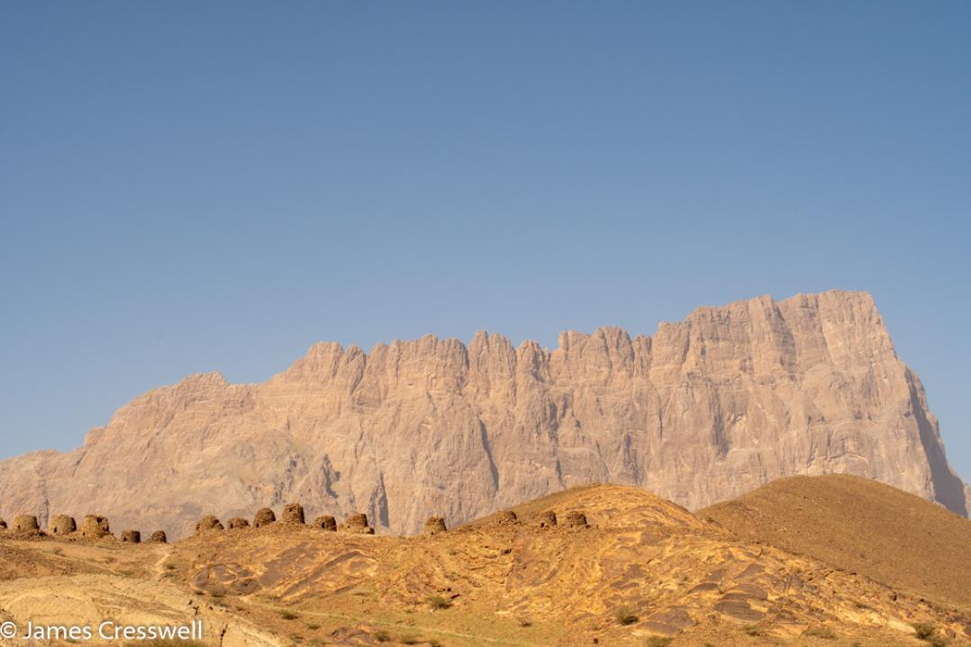 A photograph of Jebel Misht mountain and the Al Ayn beehive tombs World Heritage Site, taken on a GeoWorld Travel Oman geology trip, tour and holiday