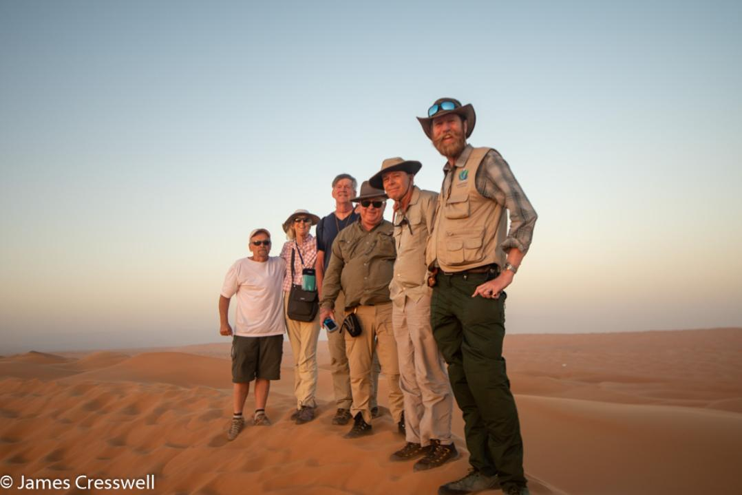 A photograph of six people standing on top of a desert dune in the Wahiba Sands, taken on a GeoWorld Travel Oman geology trip, tour and holiday
