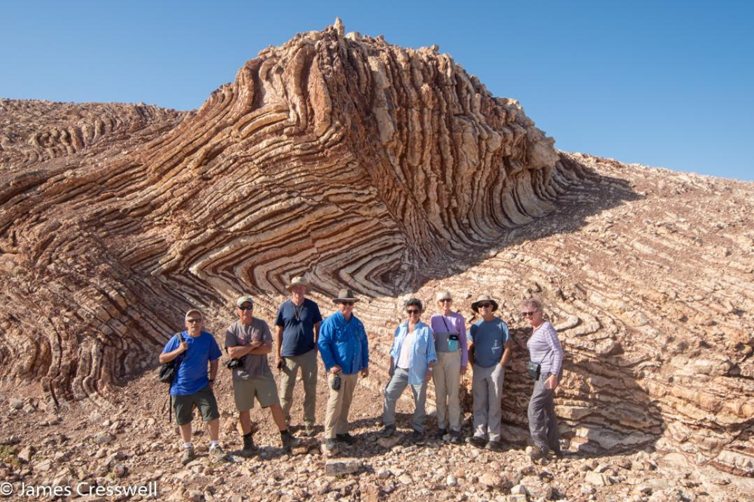 A photograph of eight people standing in front of red and white coloured folded rock, the Mother of All Outcrops in radiolarian chert, taken on a GeoWorld Travel Oman geology trip, tour and holiday