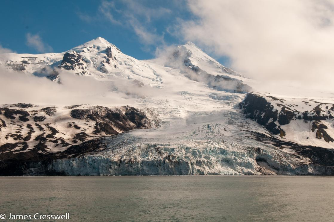 A photograph of a glacier flowing from the summit of Beerenberg volcano to the sea on Jan Mayen, taken on a PolarWorld Travel placed expedition cruise